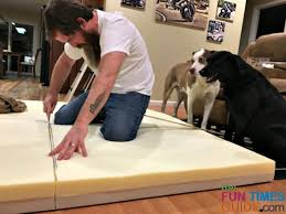 hubby cutting the memory foam pad into 4 separate pieces
