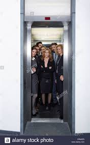 people in elevator. germany, neuss, business people standing in elevator e