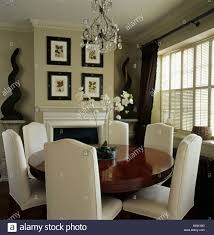 tall back cream upholstered chairs and circular antique table in beige townhouse dining room with small glass chandelier