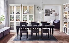 a large dining room with a black extendable dining table with chairs and glassdoor cabinets in