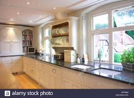 Kitchen down lighting Breakfast Bar Downlighting In Modern Galley Kitchen With White Units And Black Granite Worktops And Double Sinks In Front Of The Window Alamy Downlighting In Modern Galley Kitchen With White Units And Black