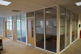 l shaped glass wall partitions with light brown wooden doors and cream concrete wall frame