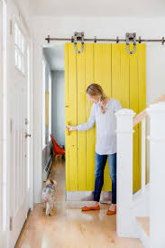 the fletts installed this sliding barn door and painted it bright yellow to add a pop of color to the hallway