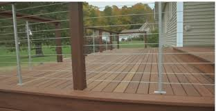 brown wood deck railing with wire cables