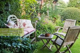 a cottage garden with shady seating area lawn and mixed borders with geraniums roses