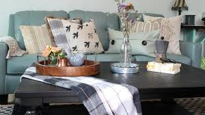 dark black brown coffee table in a living room with decor on top and a blue