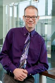ntid s scott smith md research associate professor scott smith wearing glasses purple shirt and multicolored tie