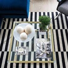 brass and glass coffee table with black and white striped rug