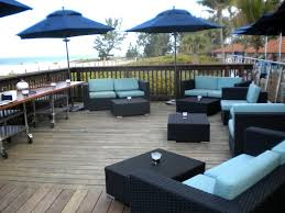 lovely blue outdoor wicker lounge furniture with light blue pad on wooden floor combined with navy blue umbrella