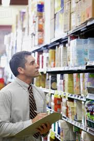 Hispanic Grocery Store Manager Writing On Clipboard Stock Photo