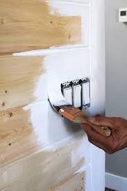 painting around the light switches on a tongue and groove wall
