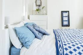 seaside bedroom furniture. White Walls, Furniture And Linen With Splashes Of Bright Blue Textiles Create A Serene Seaside Bedroom