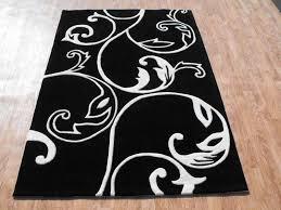 wonderful black rug idea with artistic white motif design at astonishing wooden floor design