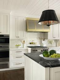 white and gold kitchen with honed black marble countertops