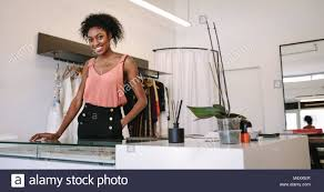 Fashion Designing Boutique Jobs Female Fashion Designer Standing At Her Desk In Her Boutique