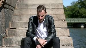 trendy looking man sitting alone outside on steps alongside a river wearing a black leather jacket and a white shirt looking away from with a sad