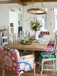 suzani fabric covers silver painted wood seats by redford house and zentique s armchairs and birch sidechairs the pine dining table is from restoration