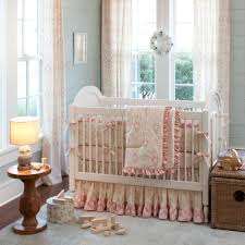 white wooden baby crib with shabby pink bedding nursery set on the rug