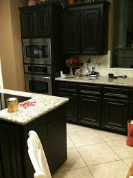 small kitchen spaces with black color staining oak kitchen cabinet with granite countertop and ceramic backsplash plus microwave storage built in ideas