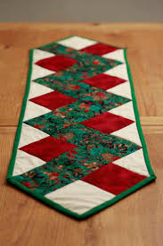 stunning green patterned christmas table runner with berries fir cones and ivy leaves dark red marbled and cream fabric zig zag quilted table runner