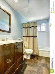 Light Brown Paint Color Bathroom Bathroom With Brown Tile Floor And Light Blue Walls Stock