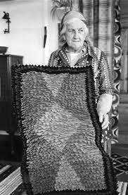 Magdalena Andersen holder et hjemmelaget teppe. - Telemark Museum /  DigitaltMuseum