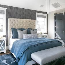 gray bedroom with blue accent wall. fabulous bedroom features an accent wall clad in black and white geometric pattern wallpaper lined with a cream velvet tufted headboard on bed dressed gray blue n