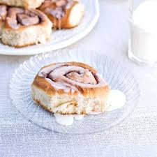 cinnamon roll on clear plate with white and stack of rolls off to the