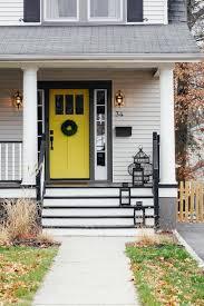 white siding black shutters dark treads porch floor yellow door