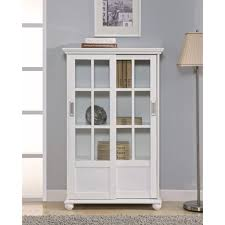 white painted wooden bookcase with glass doors combined stainless steel floorlamp and grey fur