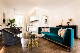 mid century living room velvet couch sofa barn farmhouse hardwood floor white brick wall diy gold brick living room furniture