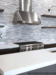 white gray backsplash white cabinets and beautiful stone counters in this kitchen