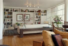 track lighting in living room. Track Lighting Living Room With White Upholstery Sofa Built In Book Shelf Two Framed Pictures And Rectangle Wooden Table A