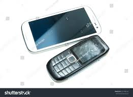 stock photo a modern smartphone and a old classic cell phone side by side