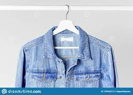 Light Gray Denim Jacket Blue Denim Jacket On White Wooden Coat Hanger On A Rod