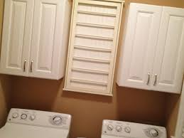 white wooden cabinet storage over double top loader washing machine also brown accent wall paint color