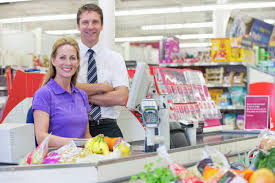 Portrait Of Supermarket Manager And Cashier At Checkout Stock