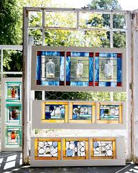 salvaged windows form the canvas for lynne s glass bottle art