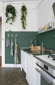 a half painted dark green wall is used as a backsplash and adds a colorful