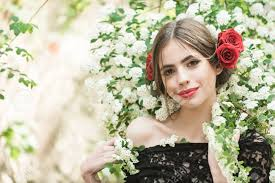 stock photo woman pretty with fashionable makeup and red lips has rose flower in hair hispanic or spanish style in black dress at white spring or