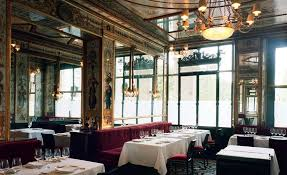 interior of le grand vefour paris a chandelier hangs from an orate ceiling down