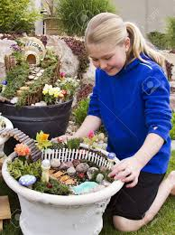 stock photo young girl helping to make fairy garden in a flower pot outdoors