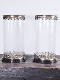 pair of arteriors seeded glass cylinder hurricanes with stylized brass bases and trim