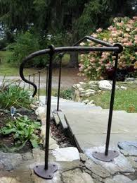 termination of hand rail this entry wrought iron railing was made from hammered textured steel pipe and solid round stock the vertical posts and hand rail