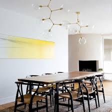 midcentury modern lighting. minimalist dining room with gold midcentury modern statement light lighting