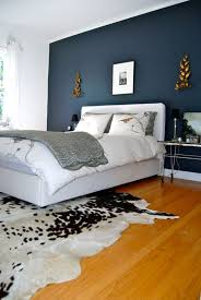 black and white cowhide area rug in a bright bedroom