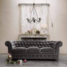 dark gray velvet tufted sofa with 3 cushions in front of fireplace with old wood wall panels rustic living room spaces ideas
