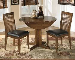 The Stuman Medium Brown 3 Pc Round Drop Leaf Dining Set Available