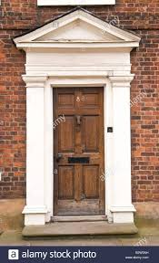 brown wooden front door with white frame and pediment on townhouse in ludlow shropshire england uk