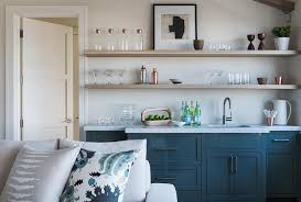 behind a light gray sofa accented with gray and blue pillows blue wet bar cabinets are adorned with dark nickel pulls and a gray marble countertop finished